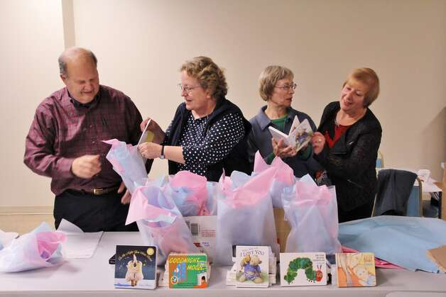 """B'nai Sholom congregants, from left,  Dr. Richard Propp, Rebecca Marvin, Mari Vosburgh and Valerie Tabak fill gift bags with books for babies. More than 300 books were delivered to Ob/Gyn Health Center Associates of Community Care Physicians in Troy to encourage expectant mothers to read to their babies before they are born.  """"Books for Babies"""" are being distributed to expectant parents by the Community Care physicians, along with a brochure explaining the importance of reading to a child even before he or she is born. Funds for Books for Babies were raised in part in memory of Vera Propp, a B'nai Sholom founder and reading teacher. Propp initiated several literacy projects in the Capital District during her lifetime. B'nai Sholom plans to continue Books for Babies and add Spanish translations of classic children?s books as well. (Photo by Ben Marvin)"""