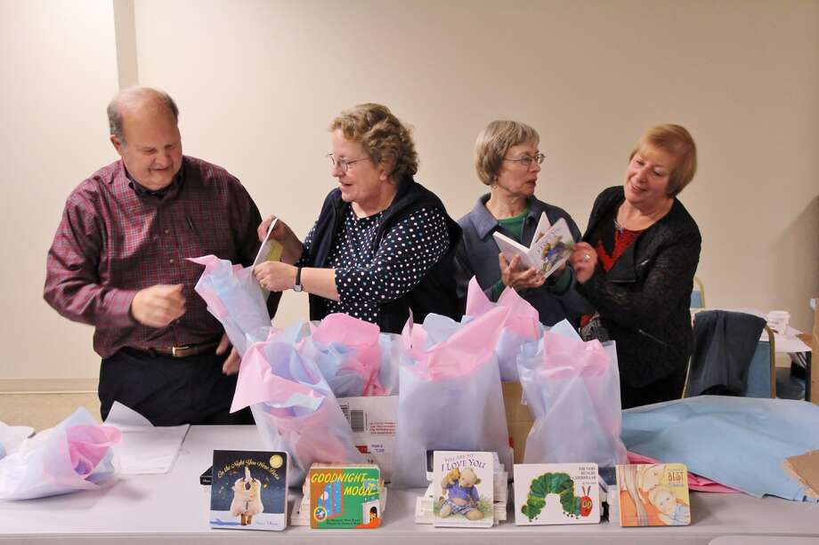 "B'nai Sholom congregants, from left,  Dr. Richard Propp, Rebecca Marvin, Mari Vosburgh and Valerie Tabak fill gift bags with books for babies. More than 300 books were delivered to Ob/Gyn Health Center Associates of Community Care Physicians in Troy to encourage expectant mothers to read to their babies before they are born.  ""Books for Babies"" are being distributed to expectant parents by the Community Care physicians, along with a brochure explaining the importance of reading to a child even before he or she is born. Funds for Books for Babies were raised in part in memory of Vera Propp, a B'nai Sholom founder and reading teacher. Propp initiated several literacy projects in the Capital District during her lifetime. B'nai Sholom plans to continue Books for Babies and add Spanish translations of classic children?s books as well. (Photo by Ben Marvin)"