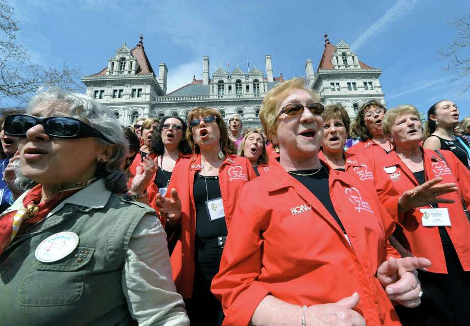 Claudia Bienenfeld of Brooklyn, left, and Jane Holden of New Jersey, right, perform a mass sing with other members of The Sweet Adelines Friday April 11, 2014, on the east steps of the Capitol in Albany, N.Y. Members of the Sweet Adelines Greater NY/NJ Region 15 were in town for their annual contest and convention which is being held at the Empire State Plaza Convention Center. (Michael P. Farrell/Times Union) Photo: Michael P. Farrell / 00026451A