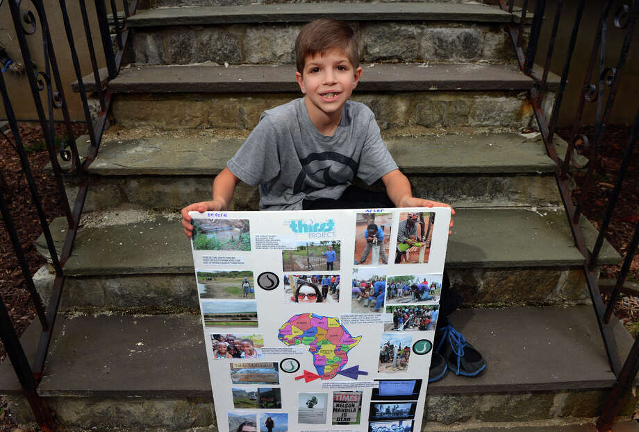 Aiden Giammarco, 9, poses with his Thirst Project presentation in front of his home Trumbull, Conn. on Friday April 11, 2014. Giammarco organized a fundraiser at his school to help have a well installed recently for a village in Africa through the non-profit organization. So far, he has raised over $1,200. Photo: Christian Abraham / Connecticut Post