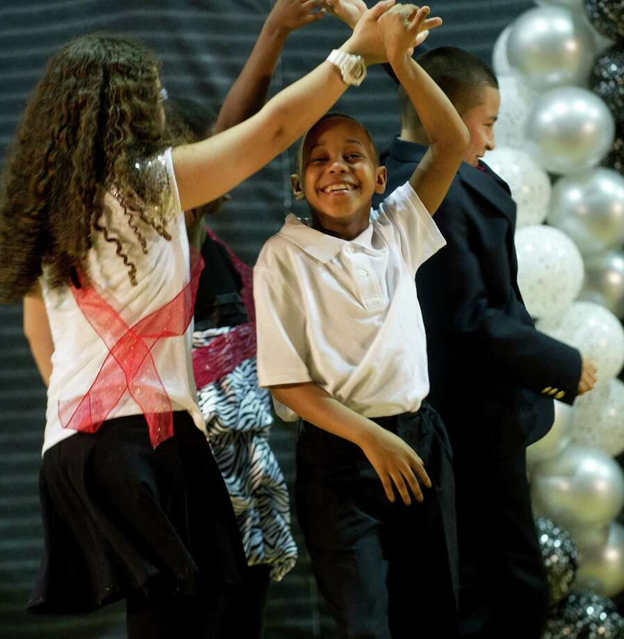 Nat Young smiles as he performs ballroom dancing with Isabella Colucci during Family Fun Night at the Boys and Girls Club in Stamford, Conn., on Friday, April 11, 2014. Photo: Lindsay Perry / Stamford Advocate