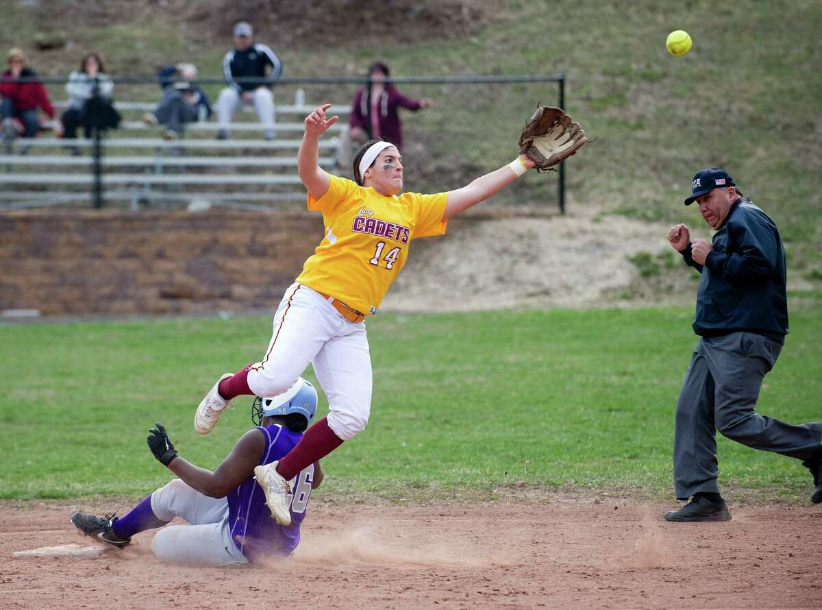 St. Joseph's Lauren Pitney leaps for the ball as Westhill's Kaira Ramon slides safely into second base during Friday's softball game at Westhill High School in Stamford, Conn., on April 11, 2014.