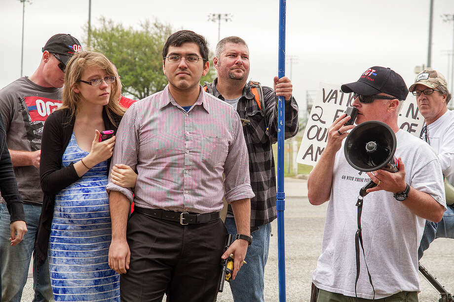Henry Vichique,center, and wife Danielle, appear at a rally with C.J. Grisham, right, president of Open Carry Texas. Photo: Alma E. Hernandez, For The San Antonio Express News