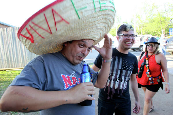 Mark Garcia grabs his hat in a gust of wind during Fiesta Oyster Bake at St. Mary's Univeristy on April 11, 2014.