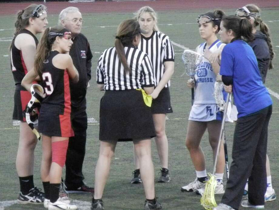 Captains and coaches meeting with the officials before the start of the Fairfield Warde-Fairfield Ludlowe girls lacrosse game on Friday, April 11 at Taft Field. The game ended in an 8-8 tie at Ludlowe. From left: Warde's Gabby Howard and Caroline Lambert, coach Tom Davis, the game officials, Ludlowe's Ellie Palazzo, coach Heather Lewsey and Ali Gorab. Photo: Reid L. Walmark / Fairfield Citizen