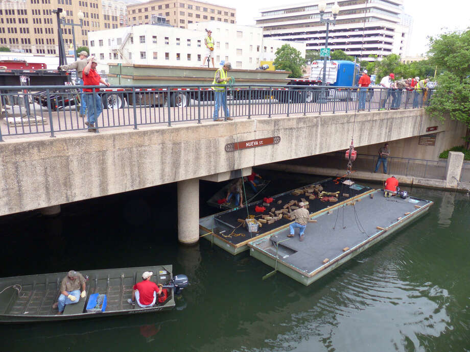 """Nueva Street over the San Antonio River is busy with activity as barges arrive on Friday, April 11, 2014, during the annual """"Barge-In Day,"""" when barges to be decorated for the upcoming Fiesta Texas Cavaliers River Parade arrive. Photo: San Antonio Express-News / San Antonio Express-News"""