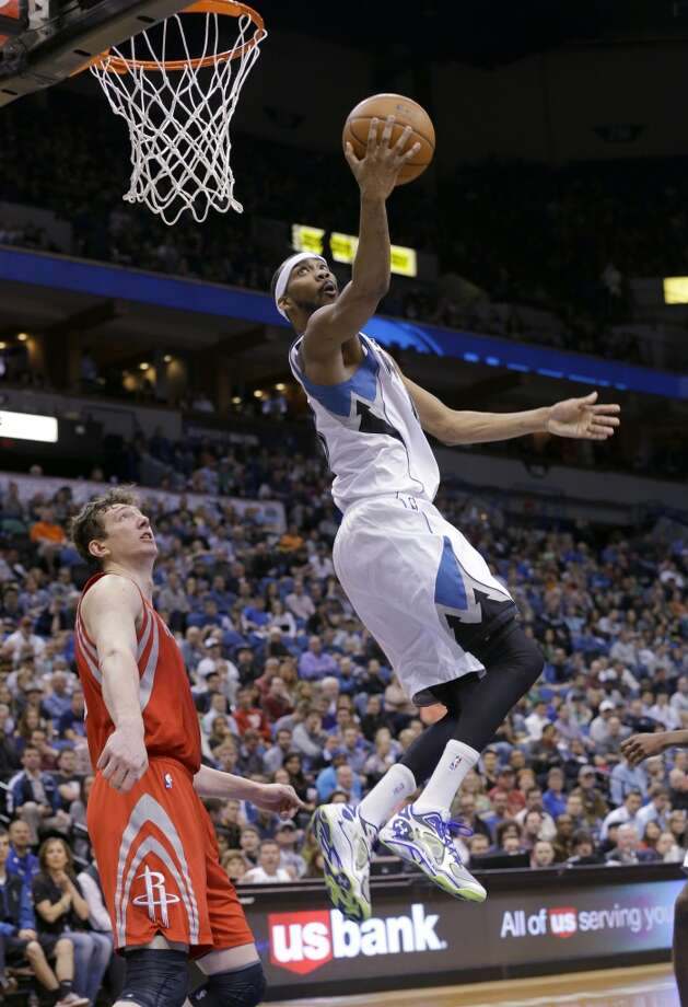 Timberwolves forward Corey Brewer (13) goes up for a shot over Rockets center Omer Asik, of Turkey. Photo: Ann Heisenfelt, Associated Press