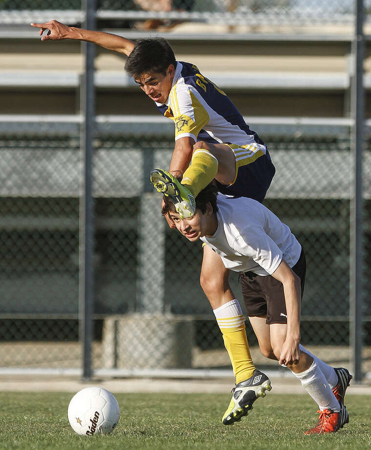 Adrian Barba of Brownsville Lopez jumps over Clark's Luis Carlos Garcia to get to the ball during the Lobos' 1-0 regional semifinal victory. Photo: Alma E. Hernandez / For The San Antonio Express-News
