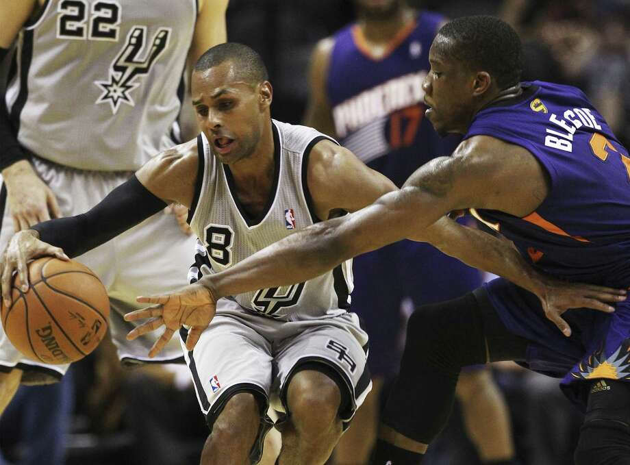Spurs guard Patty Mills is defended by Phoenix's Eric Bledsoe in the first half at the AT&T Center. Photo: Kin Man Hui / San Antonio Express-News / ©2014 San Antonio Express-News