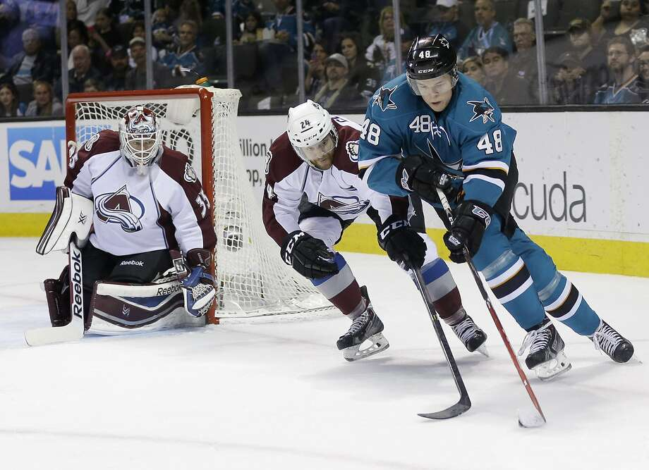 Tomas Hertl (48) works to get past Colorado's Marc-Andre Cliche as goalie J.S. Giguere follows the play. Photo: Marcio Jose Sanchez, Associated Press