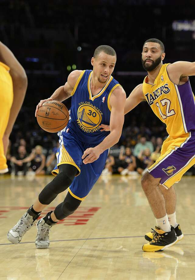 The Warriors' Stephen Curry gets past Lakers guard Kendall Marshall on his way to becoming the first Warrior with four triple-doubles in a season since Wilt Chamberlain. Photo: Richard Mackson, Reuters