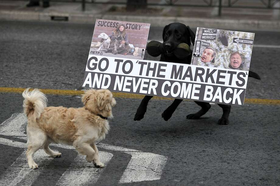 "Consider yourself warned!A canine protester's disturbing poster stops a passer-by in her tracks during a demonstration in Athens against visiting German Chancellor Angela Merkel. Greece returned to international bond markets last week amid ""renewed confidence"" in the financially strapped nation. Photo: Louisa Gouliamaki, AFP/Getty Images"