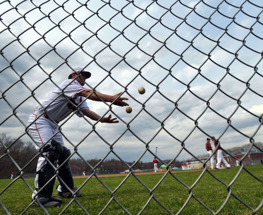 Greenwich catcher Jason Capozza does a little juggling before the high school baseball game between Greenwich High School and New Canaan High School at Greenwich, Friday afternoon, April 11, 2014. Photo: Bob Luckey / Greenwich Time
