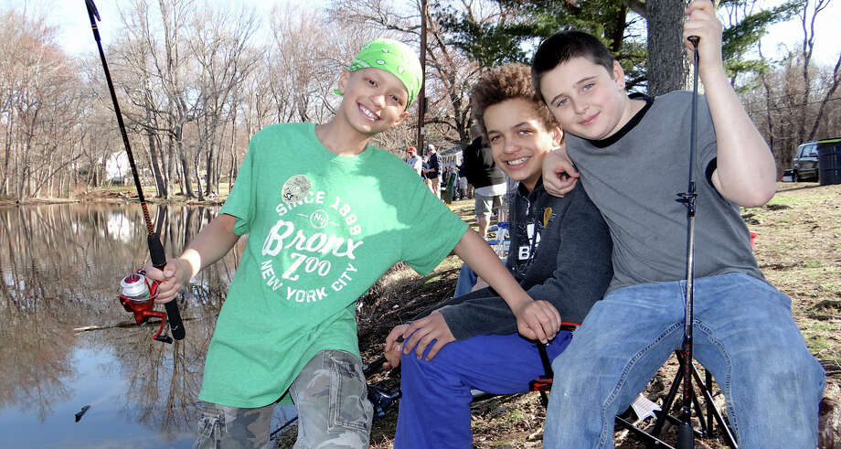 Chris and James Stead, ages 12 and 14, of Monroe, with Richie Chockey, 13, of Fairfield, at Fairfield PAL's Trout Fishing Derby at Gould Manor Park on Saturday morning. Photo: Mike Lauterborn / Fairfield Citizen