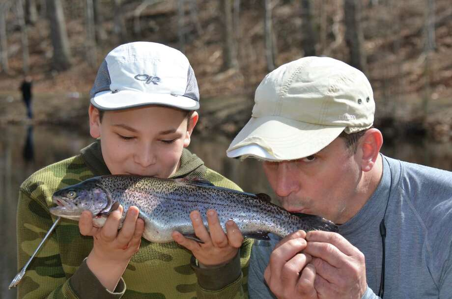 "Twelve-year-old Jimmy Curto and his father, Jim Curto, smooch the biggest catch of the day - an 18.5"" rainbow trout - at the annual fishing derby held at New Canaan's Mill Pond on Saturday, April 12, 2014. Photo: Jeanna Petersen Shepard, Freelance Photo / New Canaan News freelance"