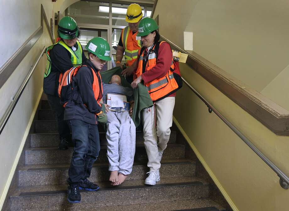 "Luc Stockholm, 11 (front), and his mother, Sophie Stockholm (right), rescue a ""victim"" with their team of response volunteers, Liz Janes and Paul Tipp, during an earthquake disaster drill. Photo: Paul Chinn, The Chronicle"