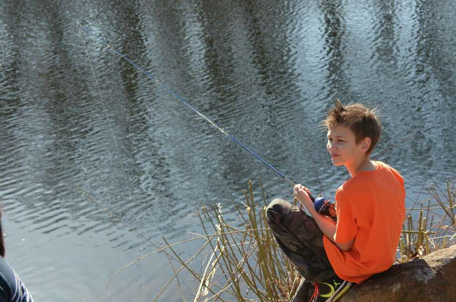 Ten-year-old Charlie Czulewics found a spot  to cast his rod at the annual fishing derby held at New Canaan's Mill Pond on Saturday, April 12, 2014. Photo: Jeanna Petersen Shepard, Freelance Photo / New Canaan News freelance