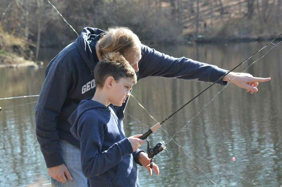 Andrew Benett gives his son Jackson some pointers at the annual fishing derby held at New Canaan's Mill Pond on Saturday, April 12, 2014. Photo: Jeanna Petersen Shepard, Freelance Photo / New Canaan News freelance
