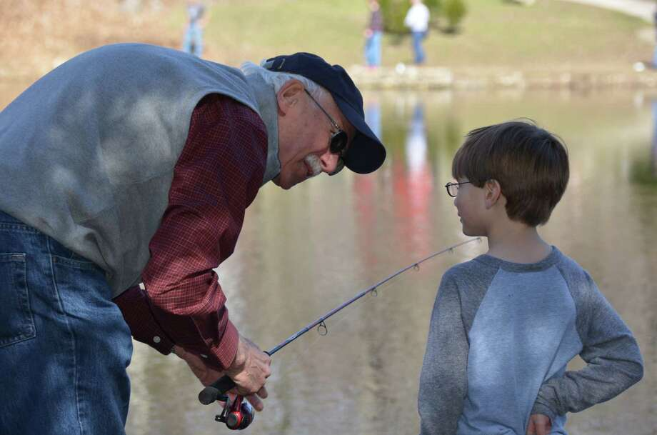 Paul Stannard teaches his grandson Ryan how to cast during the annual fishing derby held at New Canaan's Mill Pond on Saturday, April 12, 2014. Photo: Jeanna Petersen Shepard, Freelance Photo / New Canaan News freelance