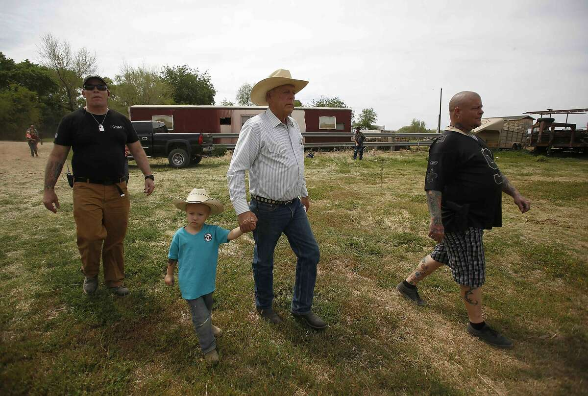 REFILE - CORRECTING LAST NAME OF GRANDSON Rancher Cliven Bundy (2nd R) walks with his grandson Braxton Logue, 3, at his home in Bunkerville, Nevada, April 11, 2014. Armed U.S. rangers are rounding up cattle on federal land in Nevada in a rare showdown with Bundy, a rancher who has illegally grazed his herd on public lands for decades, as conflict over land use simmers in western states. The standoff with the Bureau of Land Management stems in part from Bundy's belief that their right to graze the land predates the federal government's management of it, and that the county and state should ultimately have authority over lands in their boundaries. REUTERS/Jim Urquhart (UNITED STATES - Tags: AGRICULTURE CRIME LAW ENVIRONMENT ANIMALS)