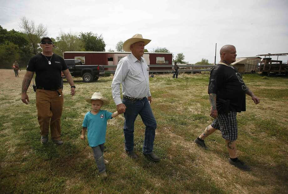 Cliven Bundy walks with grandson Braxton Logue, 3, at his home in Bunkerville, Nev. Bundy doesn't recognize federal authority on the disputed land. Photo: Jim Urquhart, Reuters