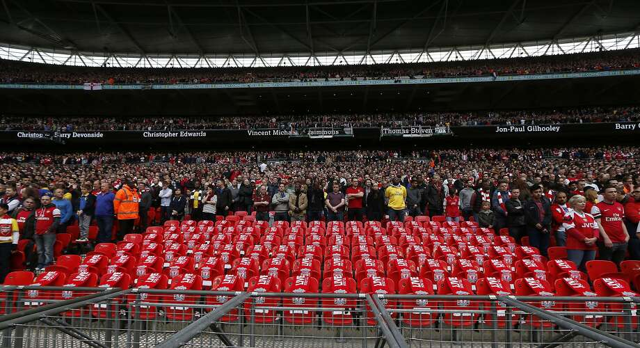 Supporters observe a minute of silence around 96 empty seats at Wembley Stadium. Photo: Sang Tan, Associated Press
