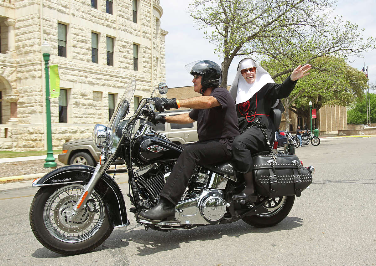 Sister Michele O'Brien and driver Dr. Mike Tilly make the courthouse as the Sisters of Charity of the Incarnate Word ride on motorcycles around the downtown plaza in New Braunfels during the second annual Harleys and Habits motorcycle fun run charity event to benefit Christus Santa Rosa Hospital on April 12, 2014.