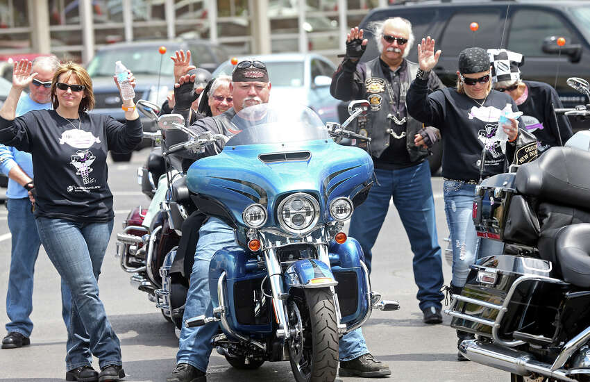Rider hold up their hands as the bikes are blessed as the Sisters of Charity of the Incarnate Word ride on motorcycles around the downtown plaza in New Braunfels during the second annual Harleys and Habits motorcycle fun run charity event to benefit Christus Santa Rosa Hospital on April 12, 2014.