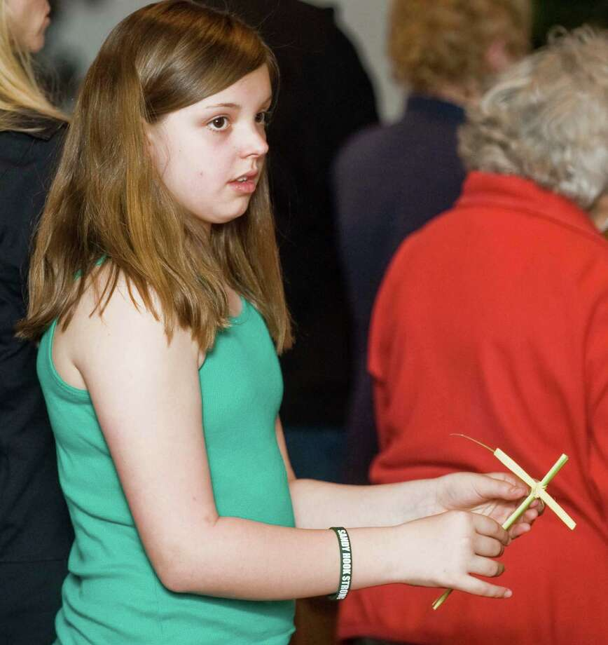 Samantha Aversano, 11, of Danbury, with a palm she made into a cross during the Saturday Palm Mass at St. Gregory the Great Church in Danbury. Saturday, April 12, 2014 Photo: Scott Mullin / The News-Times Freelance