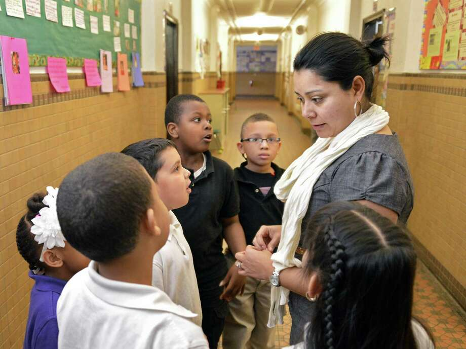 Counselor Kenia Bustillo stands last year with students at the Ark Community Charter School in Troy. The Ark school is being forced to close after this school year. (John Carl D'Annibale / Times Union) ORG XMIT: MER2014041112382334 Photo: John Carl D'Annibale / 00021573A