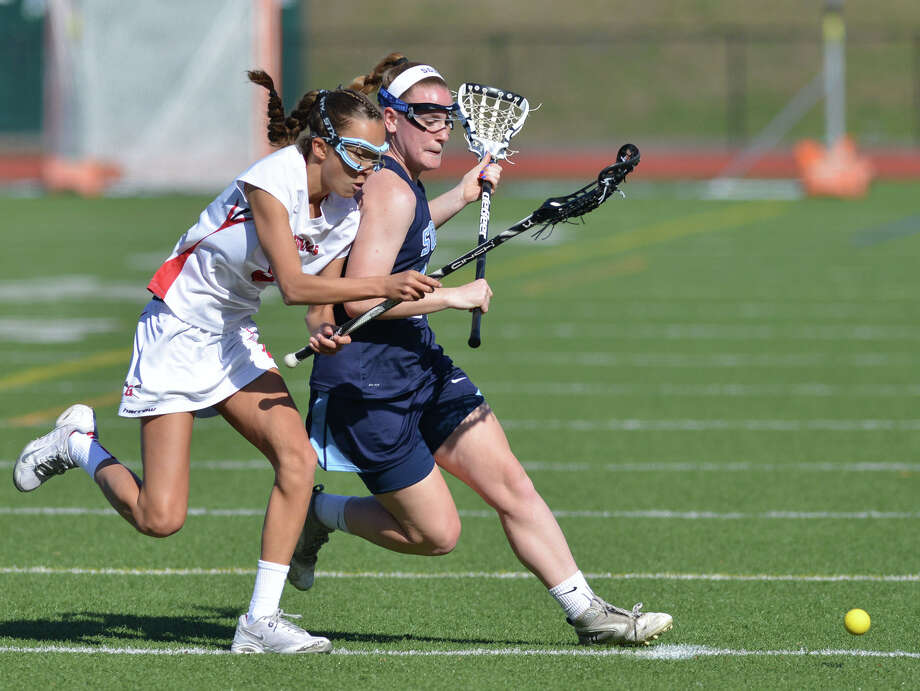 At left, Grace Paletta of Greenwich goes for the ball while being blocked by Suffern's Amy McNally, right, during the girls lacrosse match between Greenwich High School and Suffern High School at Greenwich, Saturday, April 12, 2014. Suffern defeated Greenwich, 15-5. Photo: Bob Luckey / Greenwich Time