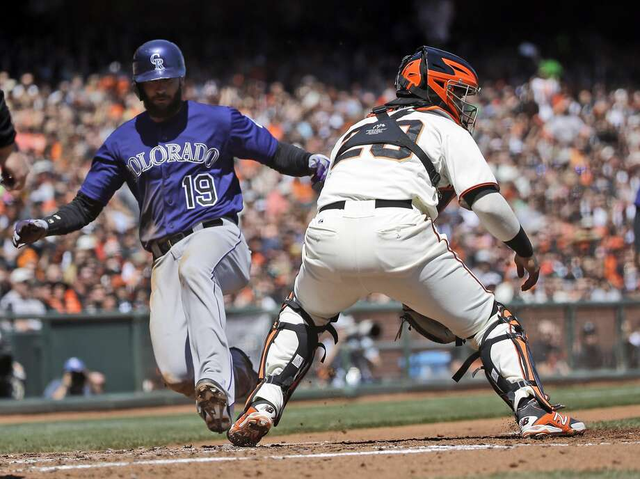 Colorado's Charlie Blackmon slides past Giants catcher Hector Sanchez in the third inning to score the game's only run. Photo: Marcio Jose Sanchez, Associated Press