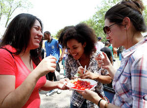 Claudia Garcia (left), Kara Gleaton and Kristen Reed share a funnel cake from Tres Flores Funnel Cakes as they celebrate their first Fiesta at the 29th Annual Taste of New Orleans April 12, 2014 at Sunken Garden Theater.  Proceeds from the three day event, hosted by the San Antonio Zulu Association, will go toward scholarships and helping those in need in San Antonio. Gleaton and Reed came from Houston to see Garcia and decided to go to the event