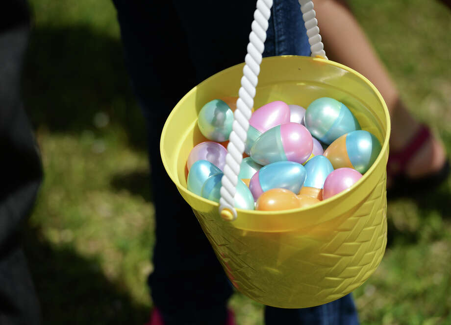A parent carries their child's pail of eggs during Saturday's Easter egg hunt at Magnolia Park.