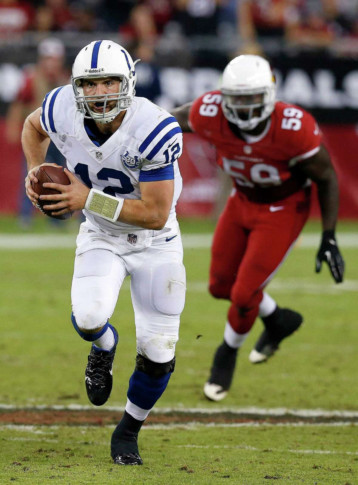 Indianapolis Colts' Andrew Luck (12) scrambles away from Arizona Cardinals' Marcus Benard (59) during the second half of an NFL football game Sunday, Nov. 24, 2013, in Glendale, Ariz. The Cardinals defeated the Colts 40-11. (AP Photo/Ross D. Franklin)