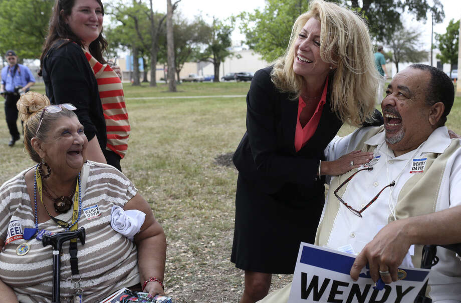 State Sen. Wendy Davis, the Democratic nominee for governor, laughs with supporters Teresa Rivera (left) and Johnny Rankin (right) at Maverick Park in San Antonio. Photo: Lisa Krantz / San Antonio Express-News / SAN ANTONIO EXPRESS-NEWS