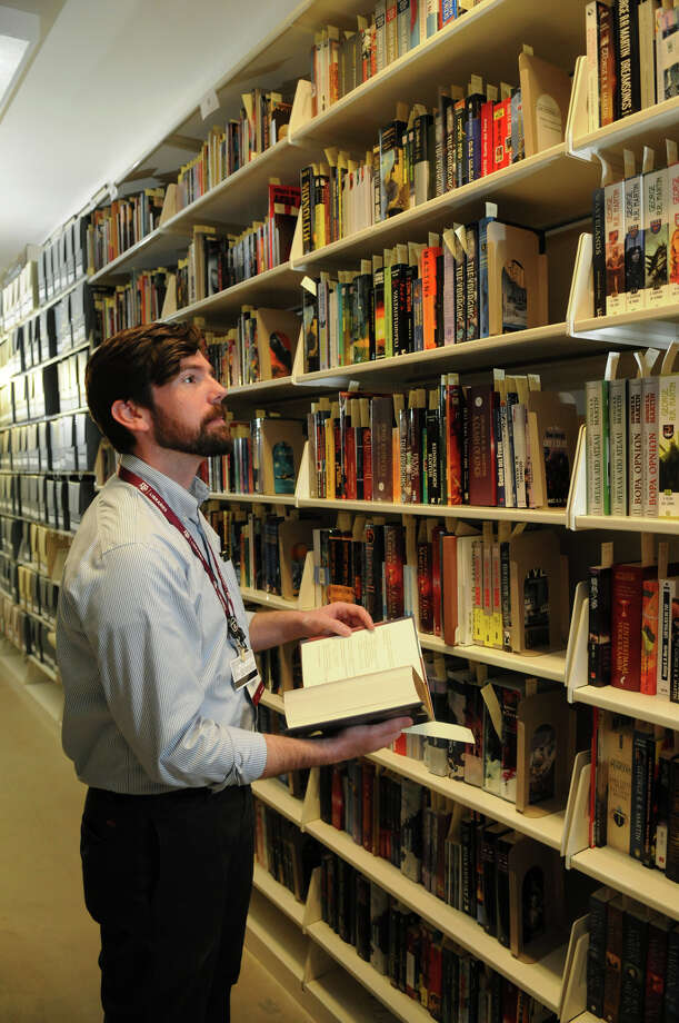 "Kevin O'Sullivan, a curator at the Cushing Memorial Library and Archives, browses ""The Wall,"" which houses works by George R.R. Martin. Photo: Jerry Baker, Freelance"