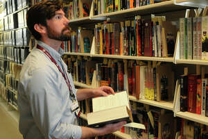 """Kevin O'Sullivan, a curator at the Cushing Memorial Library and Archives, browses """"The Wall,"""" which houses works by George R.R. Martin."""