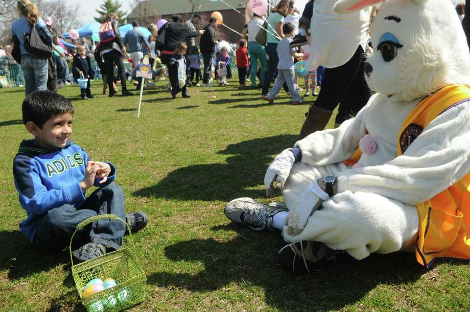 Jamie Valencia,5, takes time out with the Easter Bunny during the Greenwich Lions Club Easter Egg Hunt at Roger Sherman Baldwin Park in Greenwich, Conn., April 12, 2014. Photo: Keelin Daly / Stamford Advocate Freelance