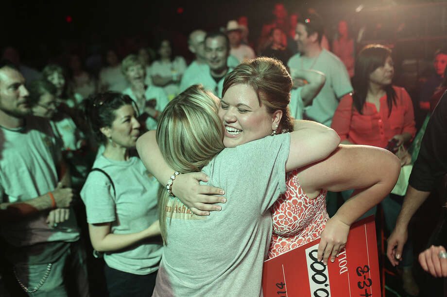 Casie McCauley (left) hugs  Ashley Trimble, the H-E-B Slim Down Showdown winner in the employee division. Trimble was awarded $10,000. Photo: Lisa Krantz / San Antonio Express-News / SAN ANTONIO EXPRESS-NEWS