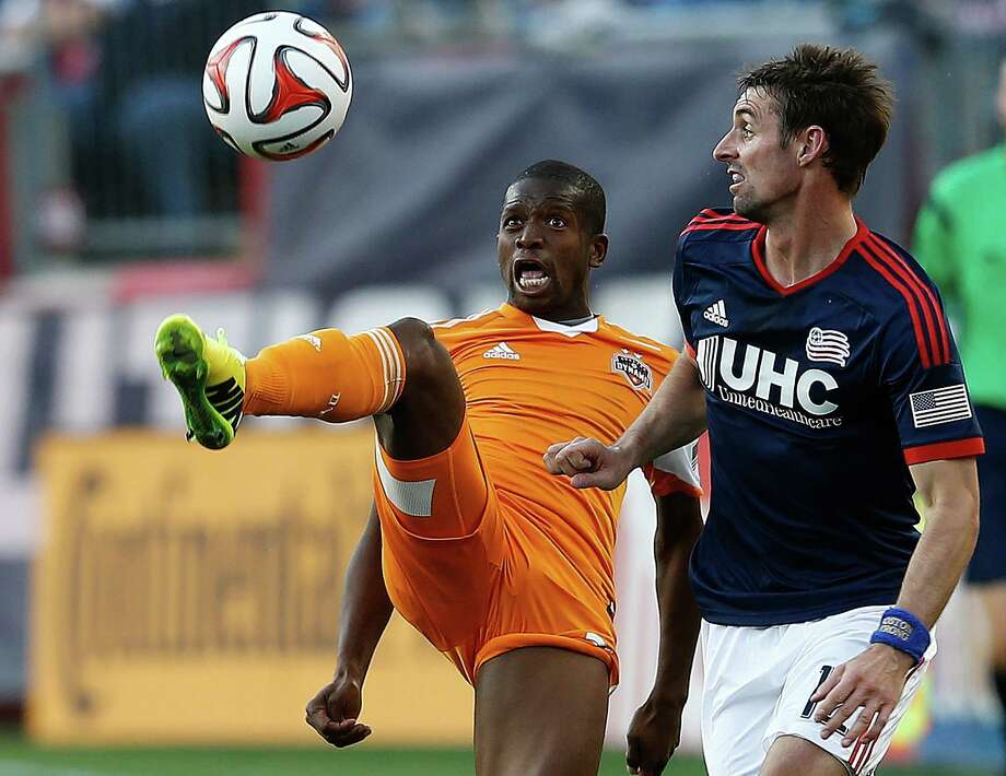 The Dynamo's Boniek Garvia, left, gets a leg up on New England's Andy Dorman as they battle for the ball in the first half of Saturday's MLS game. Photo: Jim Rogash, Stringer / 2014 Getty Images