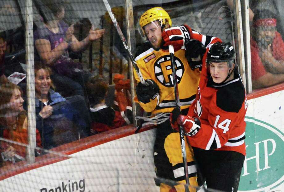 Albany Devils' #14 Reid Boucher, right, checks Providence Bruins's #7 Joe Morrow during Saturday 's game at the Times Union Center April 12, 2014, in Albany, NY.  (John Carl D'Annibale / Times Union) Photo: John Carl D'Annibale / 00026293B