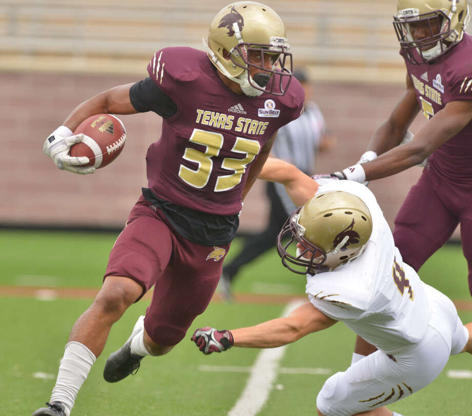 Texas State's David Farris breaks a tackle attempt by Grant Reber on a kickoff return during the annual Maroon and Gold spring game at Bobcat Stadium on Saturday. Photo: Robin Jerstad / For The Express-News / Robin Jerstad