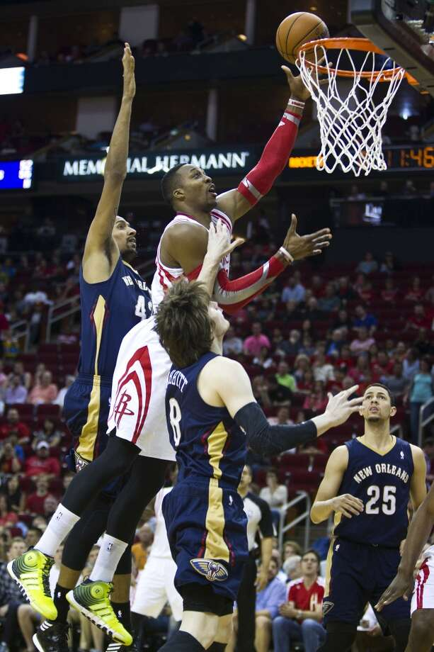 Rockets center Dwight Howard (12) drives to the basket past Pelicans center Alexis Ajinca (42) and forward Luke Babbitt. Photo: Brett Coomer, Houston Chronicle
