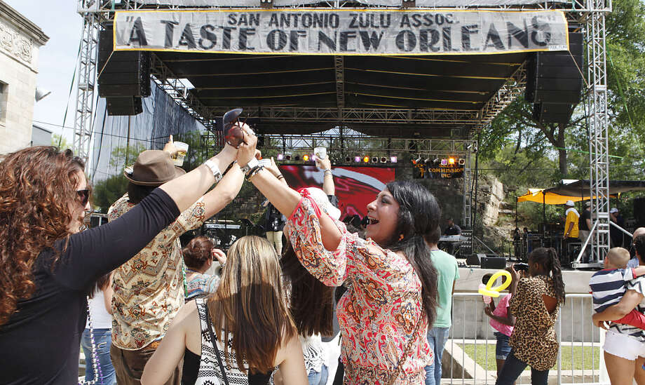 Martha Reyes Munoz (right) and Sheila Dunn cheer as the Carlton King band finishes a song during a Taste of New Orleans at the Sunken Garden Theater. This is the 13th year Munoz and Dunn have come with a group of friends from Austin for the festival. Photo: Cynthia Esparza / For The San Antonio Express-News / For the San Antonio Express-News