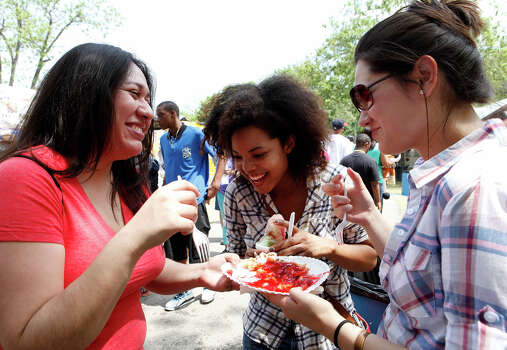 Claudia Garcia (left), Kara Gleaton and Kristen Reed share a funnel cake from Tres Flores Funnel Cakes as they celebrate their first Fiesta at the 29th Annual Taste of New Orleans April 12, 2014 at Sunken Garden Theater.  Proceeds from the three day event, hosted by the San Antonio Zulu Association, will go toward scholarships and helping those in need in San Antonio. Gleaton and Reed came from Houston to see Garcia and decided to go to the event Photo: For The San Antonio Express-News / For the San Antonio Express-News