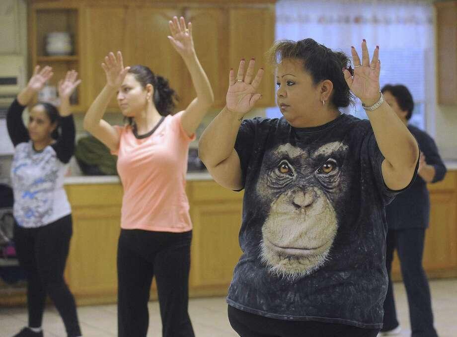 Sylvia Coronado works out in a Zumba class at Salon San Patricio as part of her program to battle diabetes. Photo: Billy Calzada / San Antonio Express-News / San Antonio Express-News