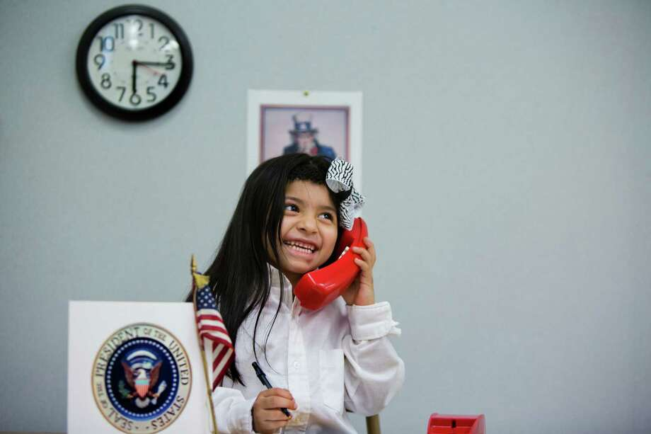 "Julianna Reyes, 5, makes a call on the ""hotline"" as president during Career Day. Photo: Marie D. De Jesus, Staff / © 2014 Houston Chronicle"