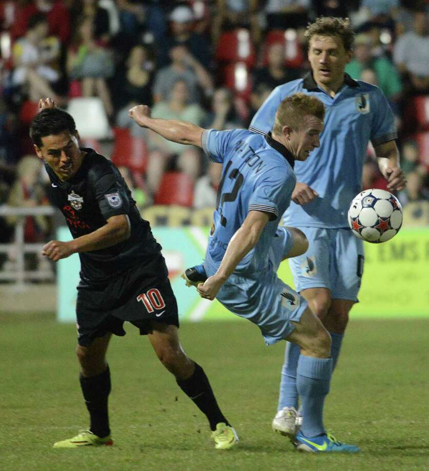Jamie Watson of Minnesota United chases the ball as Walter Restrepo of the San Antonio Scorpions watches during NASL action at Toyota Field on Saturday, April 12, 2014. Photo: Billy Calzada / Billy Calzada