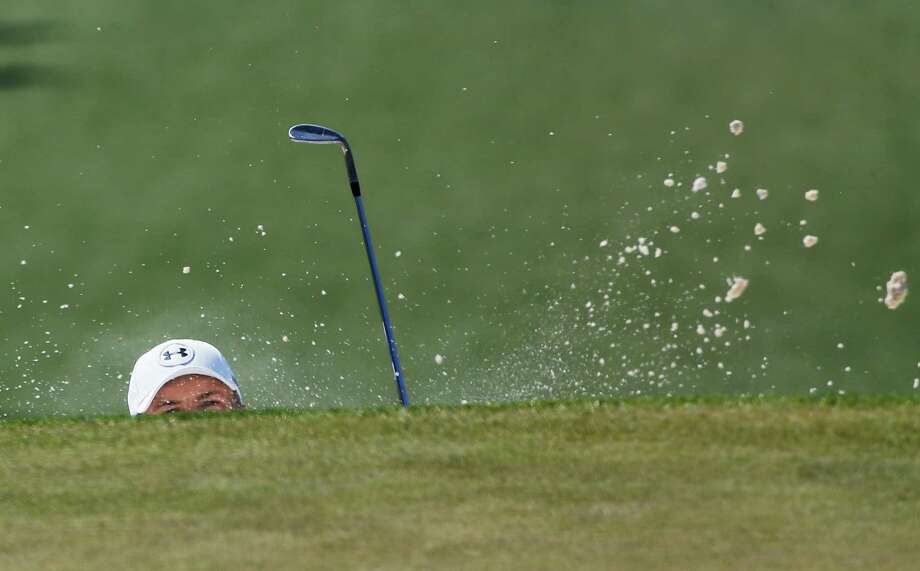 Jordan Spieth chips out of a bunker on the seventh hole during the third round of the Masters on Saturday. Photo: David J. Phillip, STF / AP